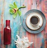 Schale des Espressosatzes mit einer Orchideenblume und -Muscheln stockfoto