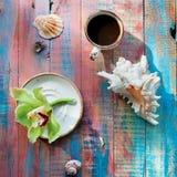 Schale des Espressosatzes mit einer Orchideenblume und -Muscheln lizenzfreies stockfoto