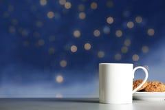 Schale des heißen Getränks mit geschmackvollen Plätzchen auf Tabelle gegen unscharfe Lichter Bokeh Effekt lizenzfreie stockfotos