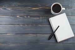 Schale des heißen Kaffees und des Anmerkungsbuches auf dem Arbeitsablauf auf den grauen Weinleseholztisch Lizenzfreie Stockbilder