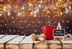 Schale des heißen Kaffees und der Tafel mit frohen Weihnachten der Wörter Stockfoto