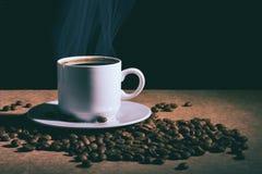 Schale des heißen Kaffees und der Untertasse auf einer braunen Tabelle Dunkler Hintergrund stockfotografie