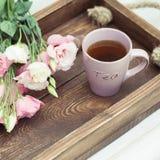 Schale des heißen Tees und des rosa Eustoma blüht junge gelbe Blume gegen weißen Hintergrund Lizenzfreie Stockfotografie