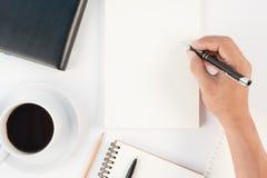 Schale des heißen Kaffee- und Mannhandschriftnotizbuches auf weißem backgr Stockfotos