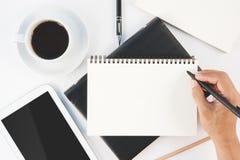 Schale des heißen Kaffee- und Mannhandschriftnotizbuches auf weißem backgr Lizenzfreie Stockbilder