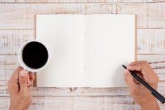 Schale des heißen Kaffee- und Mannhandschriftnotizbuches auf weißem Holz t Stockbild