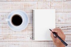 Schale des heißen Kaffee- und Mannhandschriftnotizbuches auf weißem Holz t Stockfotografie