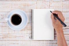 Schale des heißen Kaffee- und Mannhandschriftnotizbuches auf weißem Holz t Stockbilder