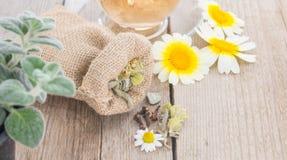 Schale des Kamillenteen mit Kamille und des Beutels mit Kräutern auf rustikalem hölzernem Hintergrund stockfoto