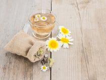 Schale des Kamillenteen mit Kamille und des Beutels mit Kräutern auf rustikalem hölzernem Hintergrund stockbild