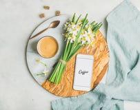 Schale des Morgenkaffees, des Eimers Blumen und des Handys Stockfotografie