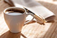 Schale des schwarzen Kaffees, der Zeitung und des Stiftes gegen Stockbilder