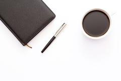 Schale des schwarzen Kaffees und des schwarzen Tagesplaners mit Stift auf weißem Hintergrund minimales Geschäftskonzept Stockbild