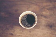 Schale des Tropfens des frischen heißen Kaffees auf der hölzernen Tabelle lizenzfreie stockbilder