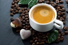Schale Espresso auf Kaffeebohnen Hintergrund und Pralinen Stockfoto