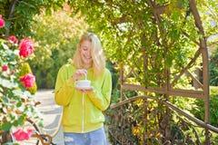 Schale Freude Hedonismus und Feinschmecker Genießen Sie köstlichen sahnigen Cappuccino in blühendem Garten Mädchengetränkfeinschm lizenzfreies stockfoto