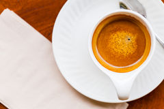 Schale frischer Espresso mit Löffel, Serviette auf Tabelle Stockfotos