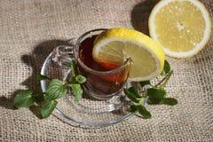 Schale gebrauter schwarzer Tee mit einer gelben Zitrone und einer grünen Minze Stockbild