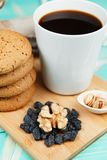 Schale geschmackvoller Kaffee mit Nüssen und Keksen über Weinleseholztisch Stockbild