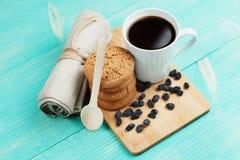 Schale geschmackvoller Kaffee mit Rosinen und Keksen über Weinleseholztisch Stockbilder