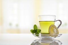 Schale grüner Tee mit Vorderansicht der Minze und der Zitrone stockbild