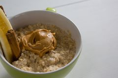 Schale Hafer mit Erdnussbutter und Zimtstangen Stockfotografie