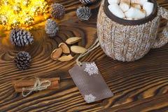 Schale heiße Schokolade mit Eibischen, Nüssen und Zimt auf einer Weinleseholzoberfläche mit Weihnachtslichtern auf Hintergrund Lizenzfreie Stockfotos
