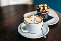 Schale heißer Bär Latte-Kunstkaffee mit köstlichem kleinem Kuchen stockbild