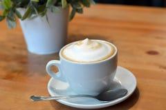 Schale heißer Cappuccino auf dem Holztisch Lizenzfreie Stockfotos