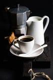 Schale heißer Espresso, Rahmtopf mit Milch-, cantucci- und mokakaffeetopf auf einem rustikalen hölzernen Brett Lizenzfreie Stockfotos