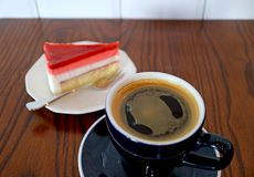 Schale heißer Kaffee auf Holztisch mit einer Scheibe des Himbeerkremeis-Kuchens im Hintergrund stockfoto