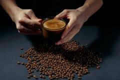 Schale heißer Kaffee in den Händen mit zerstreuten gebratenen Körnern auf dem Tisch lizenzfreie stockfotos