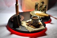 Schale heißer Kaffee mit Kaffeebohnen und kupfernem Aschenbecher mit einer großen Zigarre Lizenzfreies Stockfoto