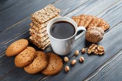 Schale heißer Kaffee sortierte mit Plätzchen zum Frühstück auf hölzerner Weinlesegrautabelle Lizenzfreies Stockbild