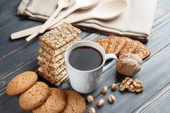 Schale heißer Kaffee sortierte mit Plätzchen zum Frühstück auf hölzerner Weinlesegrautabelle Lizenzfreie Stockbilder