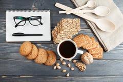 Schale heißer Kaffee sortierte mit Plätzchen zum Frühstück auf hölzerner Weinlesetabelle Schwarze Gläser auf dem Anmerkungsbuch Stockfotografie