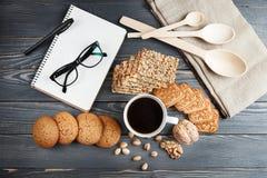 Schale heißer Kaffee sortierte mit Plätzchen zum Frühstück auf hölzerner Weinlesetabelle Schwarze Gläser auf dem Anmerkungsbuch Stockfotos
