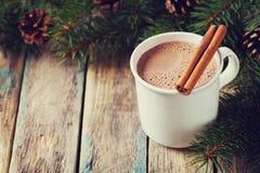 Schale heißer Kakao oder heiße Schokolade auf hölzernem Hintergrund mit Tannenbaum und Zimtstangen, traditionelles Getränk für Wi Stockbild
