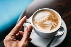 Schale heißer Lattekunstkaffee auf Holztisch stockbilder