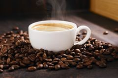 Schale hei?er Kaffee mit Dampf- und R?stkaffeebohnen stockbilder