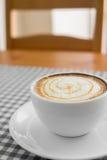 Schale heißer Cappuccino-Kaffee mit Latte-Kunst auf Plaidtabelle Lizenzfreie Stockfotos