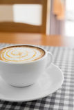 Schale heißer Cappuccino-Kaffee mit Latte-Kunst auf Plaidtabelle Lizenzfreie Stockfotografie