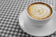 Schale heißer Cappuccino-Kaffee mit Latte-Kunst auf Plaidtabelle Stockfotos