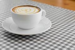 Schale heißer Cappuccino-Kaffee mit Latte-Kunst auf Plaidtabelle Stockfotografie