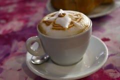 Schale italienischer Cappuccino lokalisiert auf rosa Tabelle stockfotografie