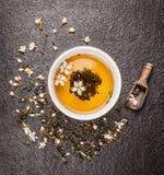 Schale Jasmintee, alte hölzerne Schaufel und frische Blumen auf dunklem Steinhintergrund Lizenzfreie Stockfotografie