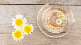 Schale Kamillentee mit Kamille auf rustikalem hölzernem Hintergrund Beschneidungspfad eingeschlossen stockfotografie