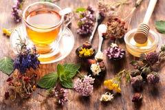 Schale Kräutertee mit wilden Blumen und verschiedenen Kräutern Stockfotografie