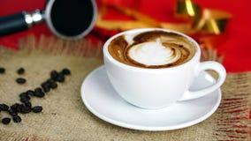 Schale Latte-, Cappuccino- oder Espressokaffee mit Milch setzte an den roten Hintergrund mit dunklen Röstkaffeebohnen Lizenzfreies Stockbild