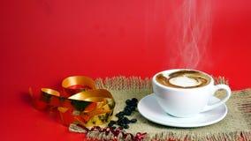 Schale Latte-, Cappuccino- oder Espressokaffee mit Milch setzte an den roten Hintergrund mit dunklen Röstkaffeebohnen Stockbilder